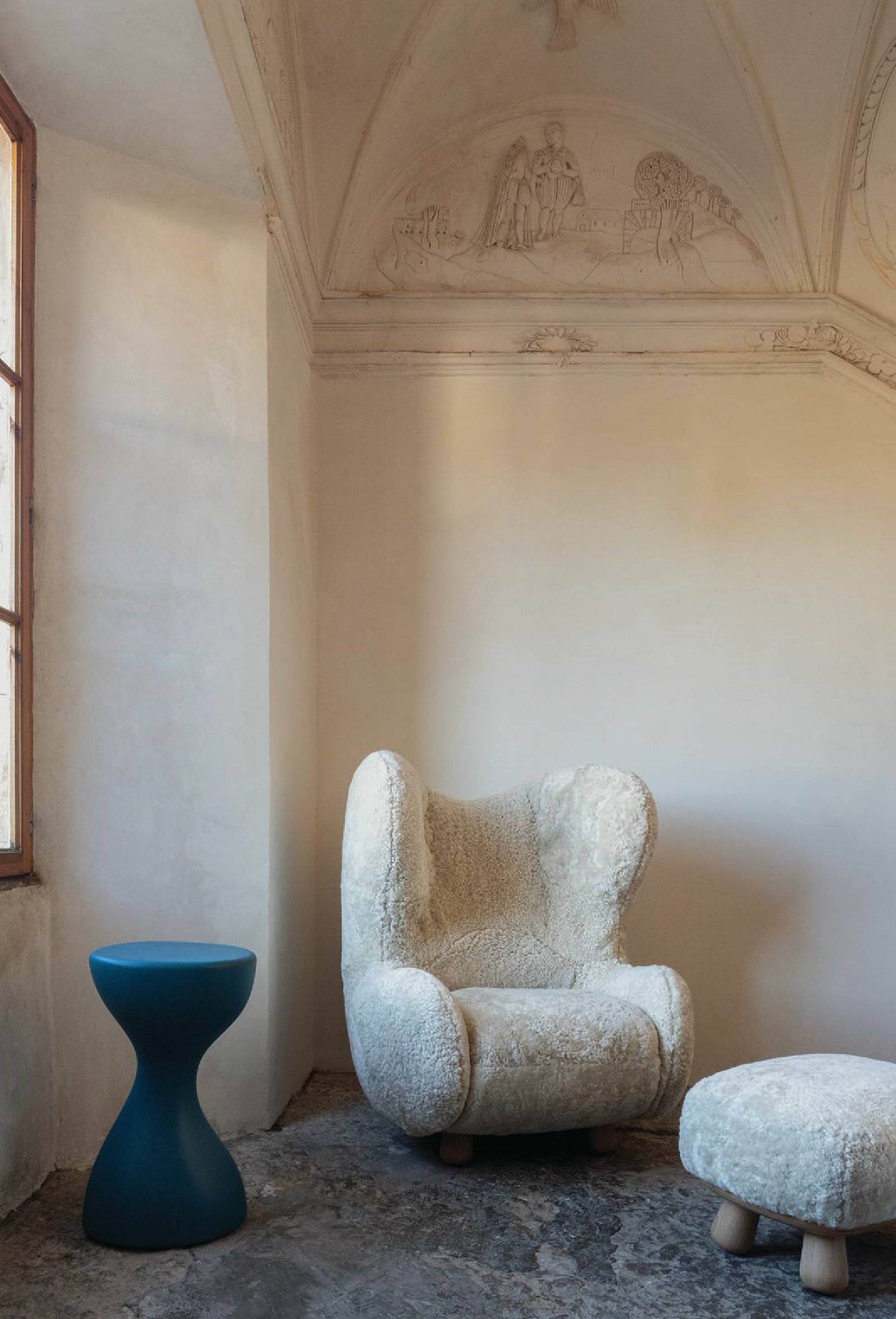 The Clifford armchair and ottoman are upholstered in sheepskin, while the Tipsy side table—made to look like a bottle—is made from tinted acrylic resin PHOTO BY GIULIO GHIRARDI