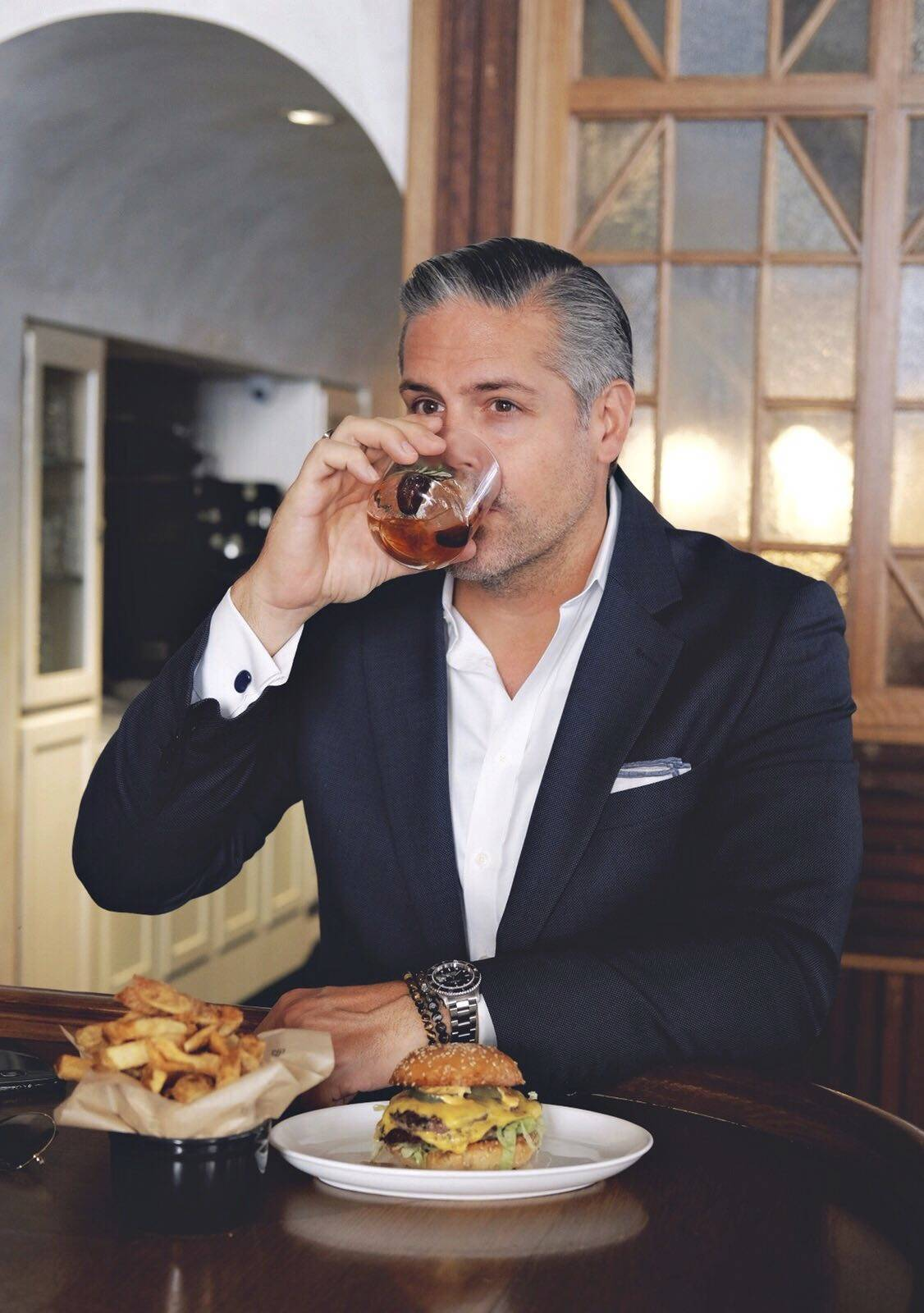 Gotham Burger Social Club's Mike Puma enjoys a drink and a burger